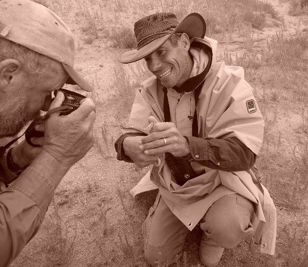 Mark Jorgensen photographing a snake Steve Bier is holding.