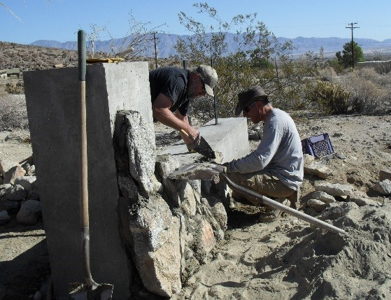 Mark Jorgensen and Steve Bier placing rocks on the entrance sign at UCI's natural reserve, Steele/Burnand Anza-Borrego Desert Research Center. (2014)